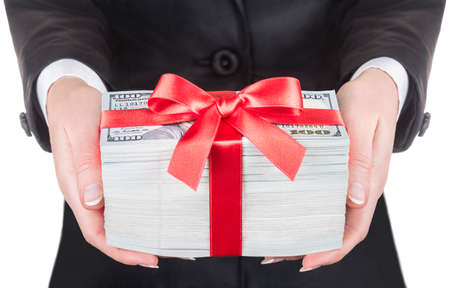 Business woman hands in black office suit give package of dollar banknotes with red bow and ribbon isolated on white background. Gift, mortgage loan, bank, deposit, profit or financial success concept 스톡 콘텐츠