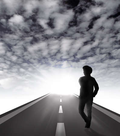 Man walking silhouette on road ahead to challenge and successful with sky background Stock Photo