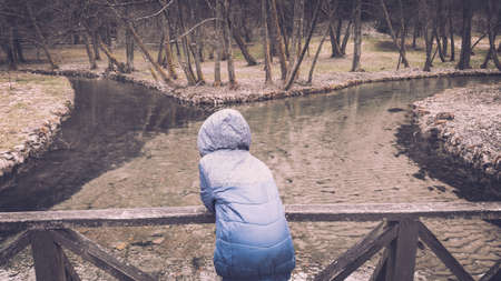 Young boy standing on the wooden bridge and enjoying the picturesque view of the river. 写真素材