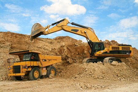 dumper truck: Backhoe loader loading dumper