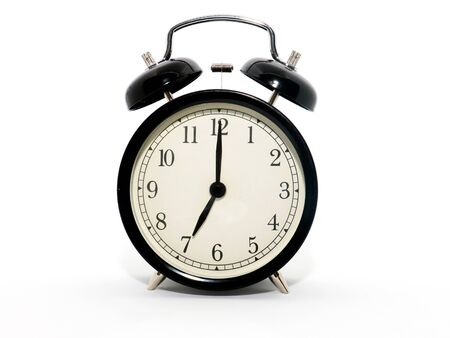 Old-style alarm clock, black and white, it's seven o'clock.