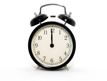 Despertador antiguo, blanco y negro, son las doce.