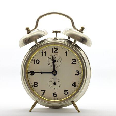 Old-style alarm clock, metal, it's quarter to twelve.