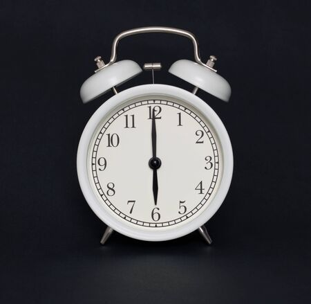 Old-style alarm clock, black and white, it's six o'clock.