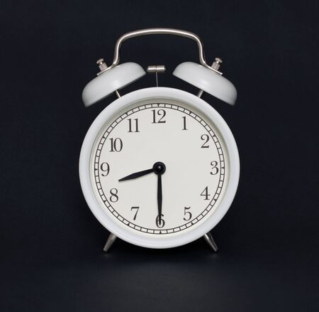 Old-style alarm clock, black and white, it's half past eight.