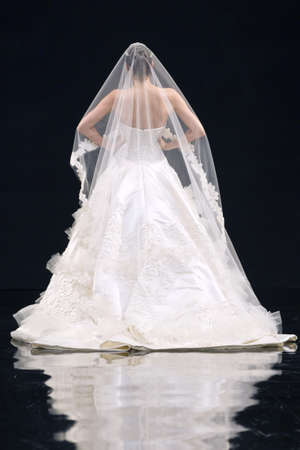 fashion model catwalk: Back view of a bride with a bridal veil on a catwalk stage.