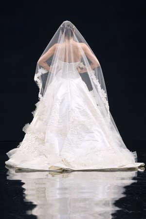 modelo en pasarela: Vista posterior de una novia con un velo de novia en un escenario pasarela.