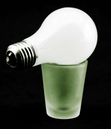 A lightbulb on top a green-lit shotglass