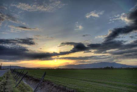 緑の草原に沈む夕日の高ダイナミック レンジ ショット。 写真素材