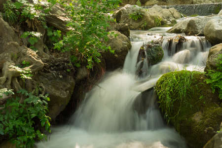 Small waterfall in the forrest.  Running small river caught in motion with silky effect.