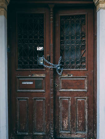Wooden doors of empty building locked with chain.