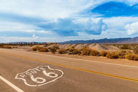 Autoroute US Route 66, avec signe sur l'asphalte et un long train en arrière-plan, près d'Amboy, en Californie. Situé dans le dessert mojave