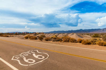 U.S. Route 66 highway, with sign on asphalt and a long train in the background, near amboy, california. Located in the mojave dessert 版權商用圖片 - 67579580