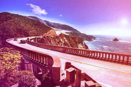 Bixby Creek Bridge on Highway #1 at the US West Coast traveling south to Los Angeles, Big Sur Area - Picture in a dreamy look with purple fall color look Stock Photo