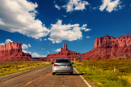 western usa: Highway in Monument Valley, Utah  Arizona, USA - Picture with road and cars driving towards the hills. Photo made during a road trip throughout the western states. Stock Photo