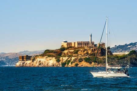 delincuencia: Isla de Alcatraz con prisión y yate en la bahía de San Francisco, California, EE.UU.