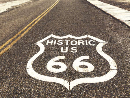 Historic US Route 66 highway sign on asphalt in Oatman, Arizona, United States. The picture was made during a motorcycle road trip through the south western states of USA.
