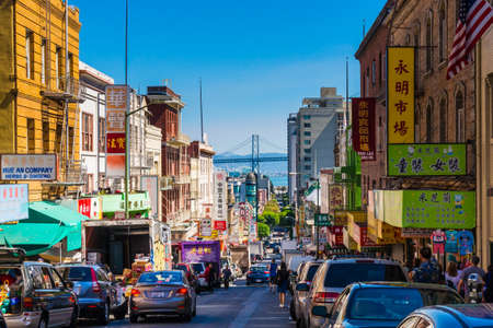 San Francisco - September 20, 2015: Downtown city life in a busy street of Chinatown San Francisco. View with many people, shops and cars - lookout to the Oakland Bay Bridge.