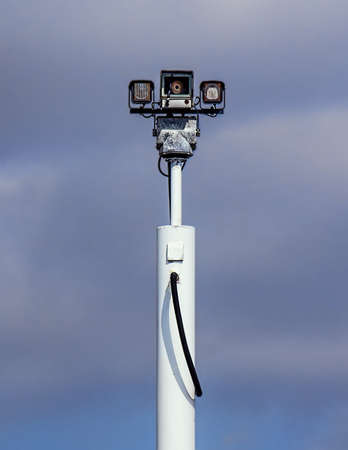 metal post: Remotely controlled security camera high on metal post on a blue sky bacground  Stock Photo