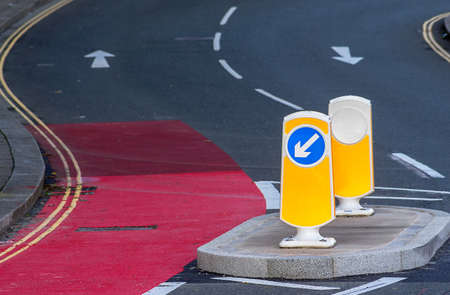 generic location: Road safety directional arrow on illuminating bollard standing in the middle of a winding, colorful road.