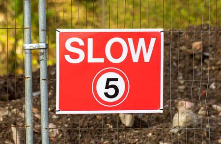 rood teken: Lage limiet voor de veiligheid van de snelheid wordt gepost op vijf mijl per hour.A rood teken opknoping op een metalen hek.