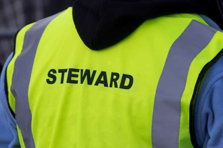 high visibility: Security staff in a high visibility,yelow, fluorescent tabard, stewarding at an outdoor event.