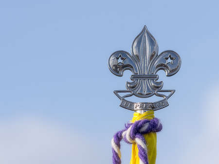 traditionally french: Silver symbol ( Fleur de lys)  with the words( Be Prepared) on top of a flag visible against the blue, clear sky.
