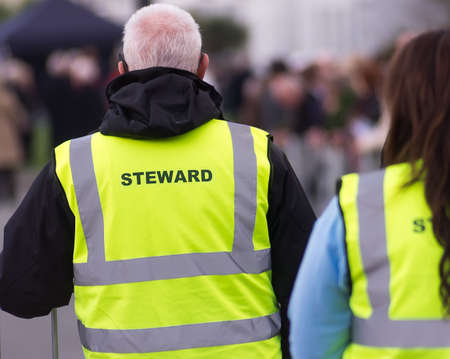 Security staff in a high visibility,yelow, fluorescent tabard, stewarding at an outdoor event.