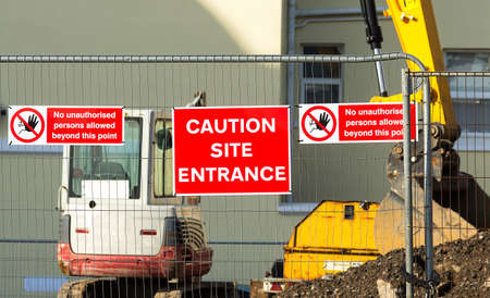 Caution sign at entrance to construction site.Red plaque hanging on the fence in the middle between the two arrays speaking about the ban on entry to the site.In the background you can see the construction site and construction machinery. Stock Photo