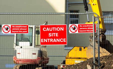 señales de seguridad: Muestra de la precaución en la entrada a la construcción site.Red placa que cuelga en la cerca en el medio entre las dos matrices que hablan acerca de la prohibición de entrada a la site.In el fondo se puede ver la obra de construcción y maquinaria de construcción. Foto de archivo