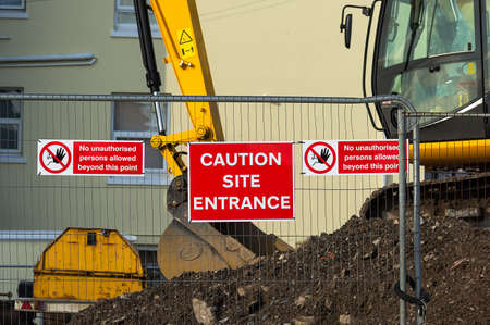 construction machines: Caution sign at entrance to construction site.Red plaque hanging on the fence in the middle between the two arrays speaking about the ban on entry to the site.In the background you can see the construction site and construction machinery. Stock Photo