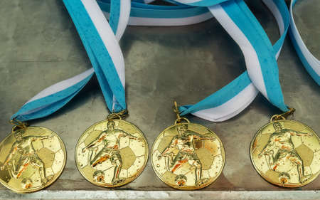winning pitch: Gold medals for a winner or champion.