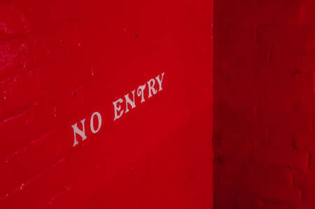 do not enter warning sign: White NO ENTRY inscription on a brick wall painted red.