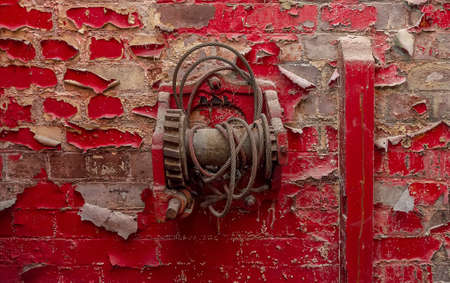 windlass: Old windlass suspended from a ruined red wall. Stock Photo