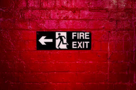 wayout: Sign Informing about the fire escape hung on a brick wall painted red. Stock Photo