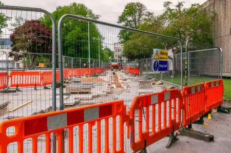 Demolished sidewalk during the pavement repair fenced temporary fence panels which have a hanging warning sign. In the background is a digger. Stock Photo