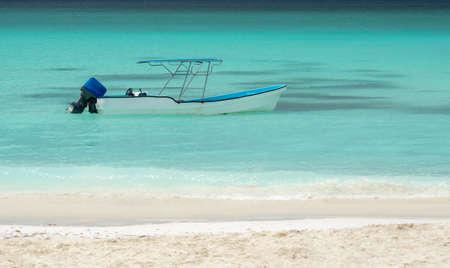 Motorboat moored on the beach of Saona Island in the Caribbean Sea.