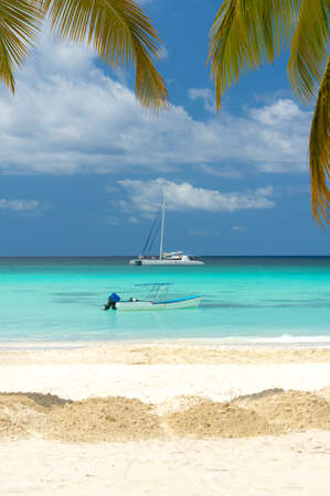 Motorboat and Catamaran with tourists moored on the beach of Saona Island in the Caribbean Sea. Stock Photo