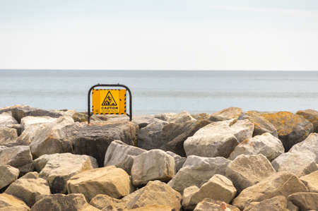 Warning sign set on the stones on the sea front. Stock Photo