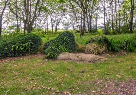 A sculpture depicting a sleeping woman in an old English garden.