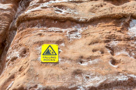 Warning sign of falling stones hanging on a rock. Stock Photo