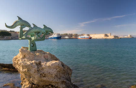A sculpture depicting four dolphins standing at a harbor on the island of Rhodes Stock Photo
