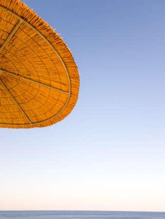 A straw beach umbrella on a background of blue sky. Stock Photo