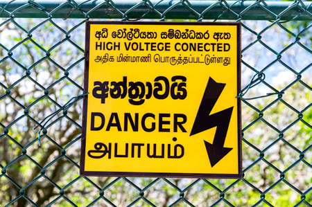 Yellow warning sign hanging on a wire fence