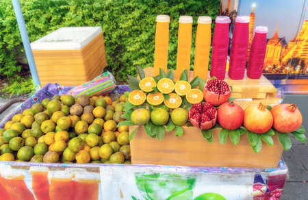 Oranges and pomegranates and fresh juice from these fruits put up for sale on a street in Bangkok. Stock Photo