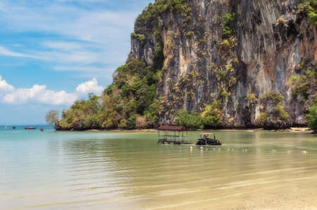 Tractor with a trailer adapted for transporting tourists from boats ashore near Railay Beach in Krabi, Thailand. Stock Photo