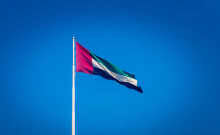The flag of the United Arab Emirates waving on the mast against the blue sky.