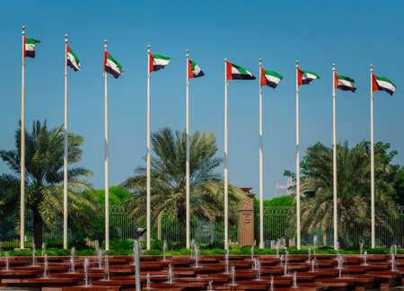 Flags of the United Arab Emirates waving on poles against the blue sky in front of the hotel in Abu Dhabi.
