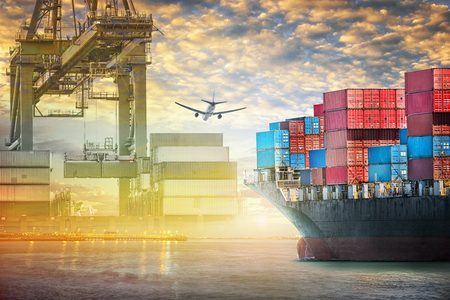 夕焼け空、貨物輸送、港のポート クレーン橋とコンテナー貨物船と貨物機出荷 写真素材