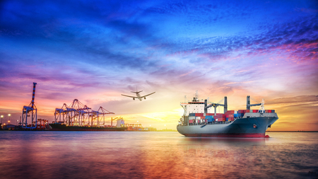 Logistics and transportation of international container cargo ship and cargo plane with ports crane bridge in harbor at twilight sky for logistics import export background and transport industry.
